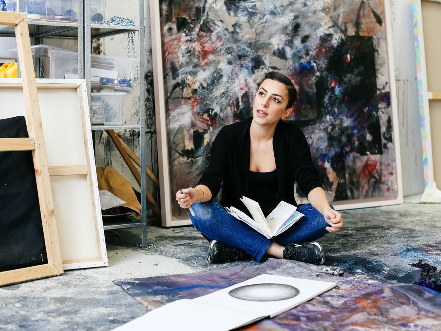 Woman sat on floor surrounded by artwork in the studio