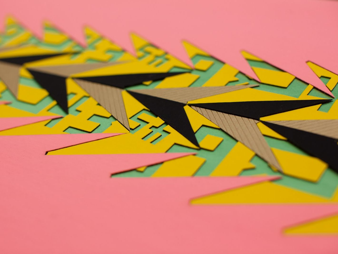 Patterns cut into pink green yellow and brown card