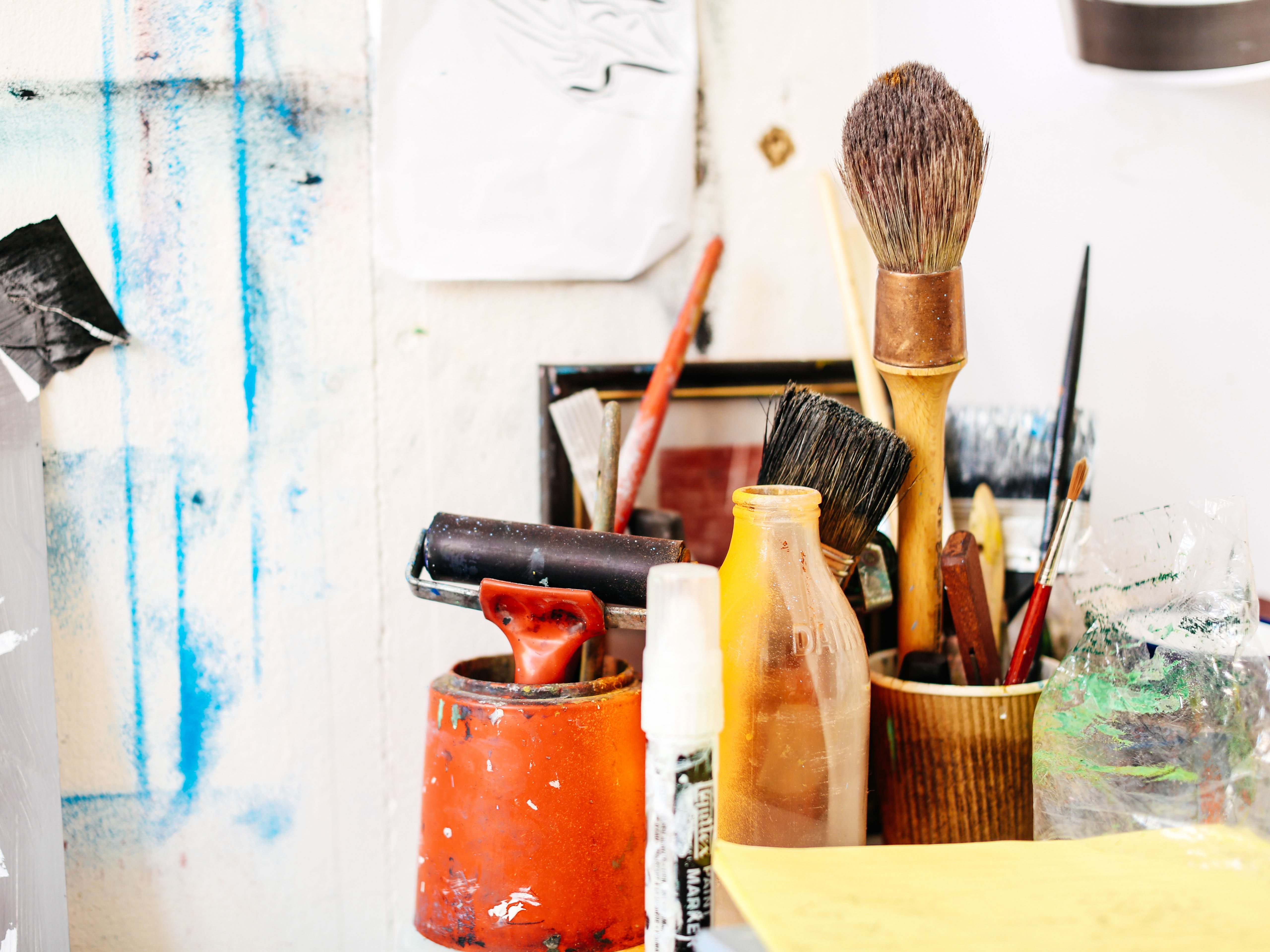Collection of art tools and materials including paint and paintbrushes