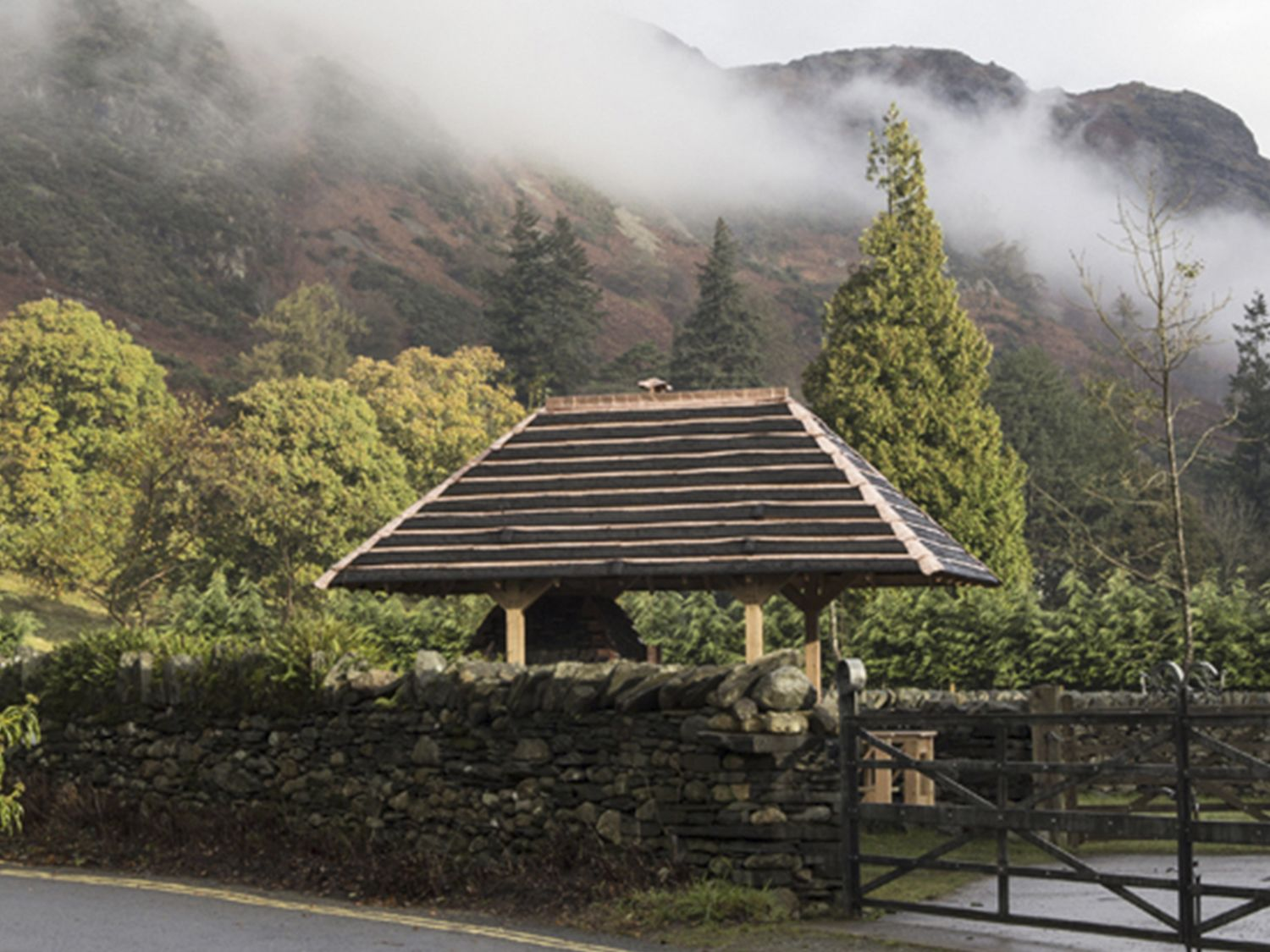 Photograph of a stone wall with a small roofed structure behind it and a forest in the background
