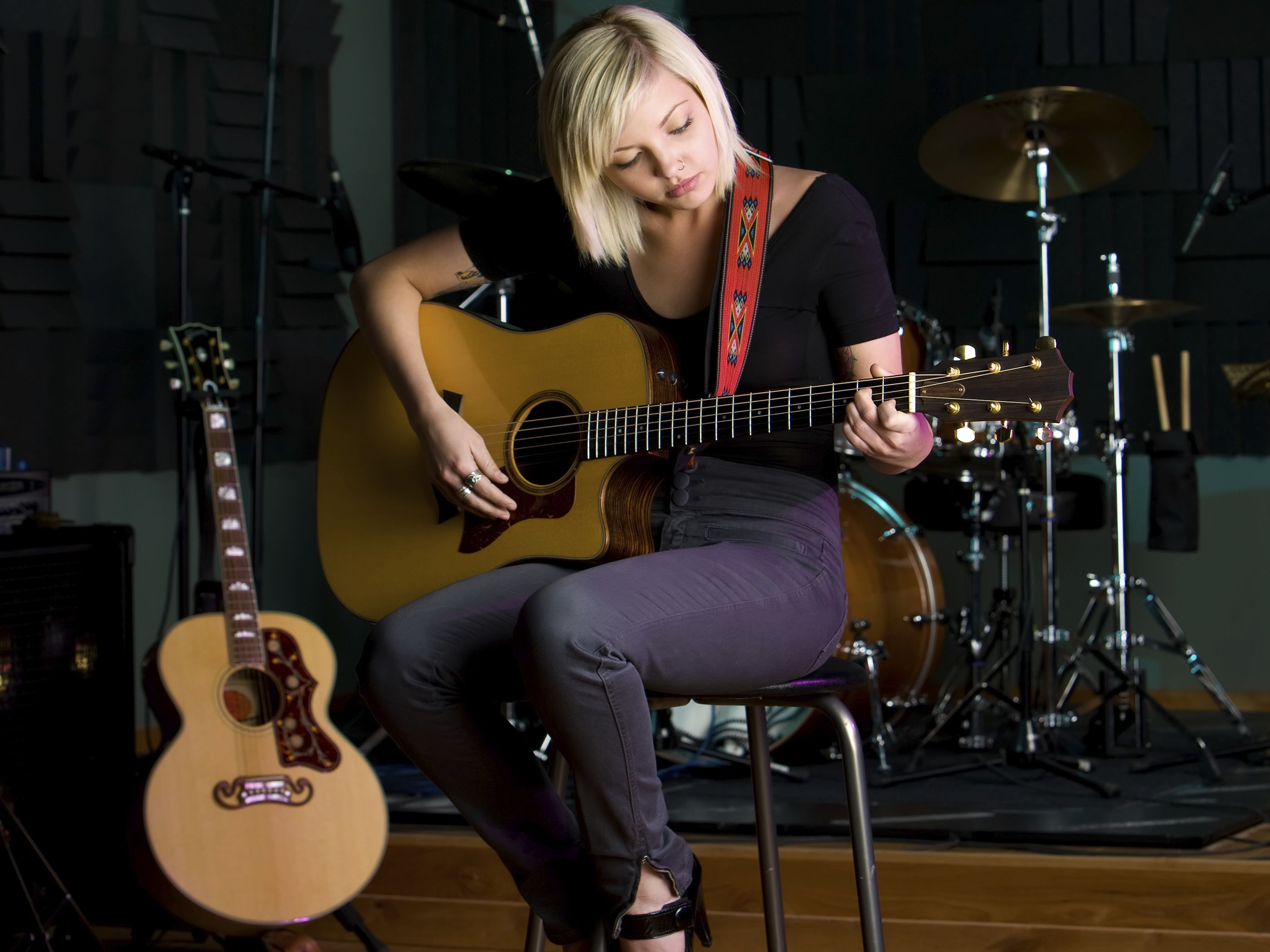Woman sitting on a stool playing guitar