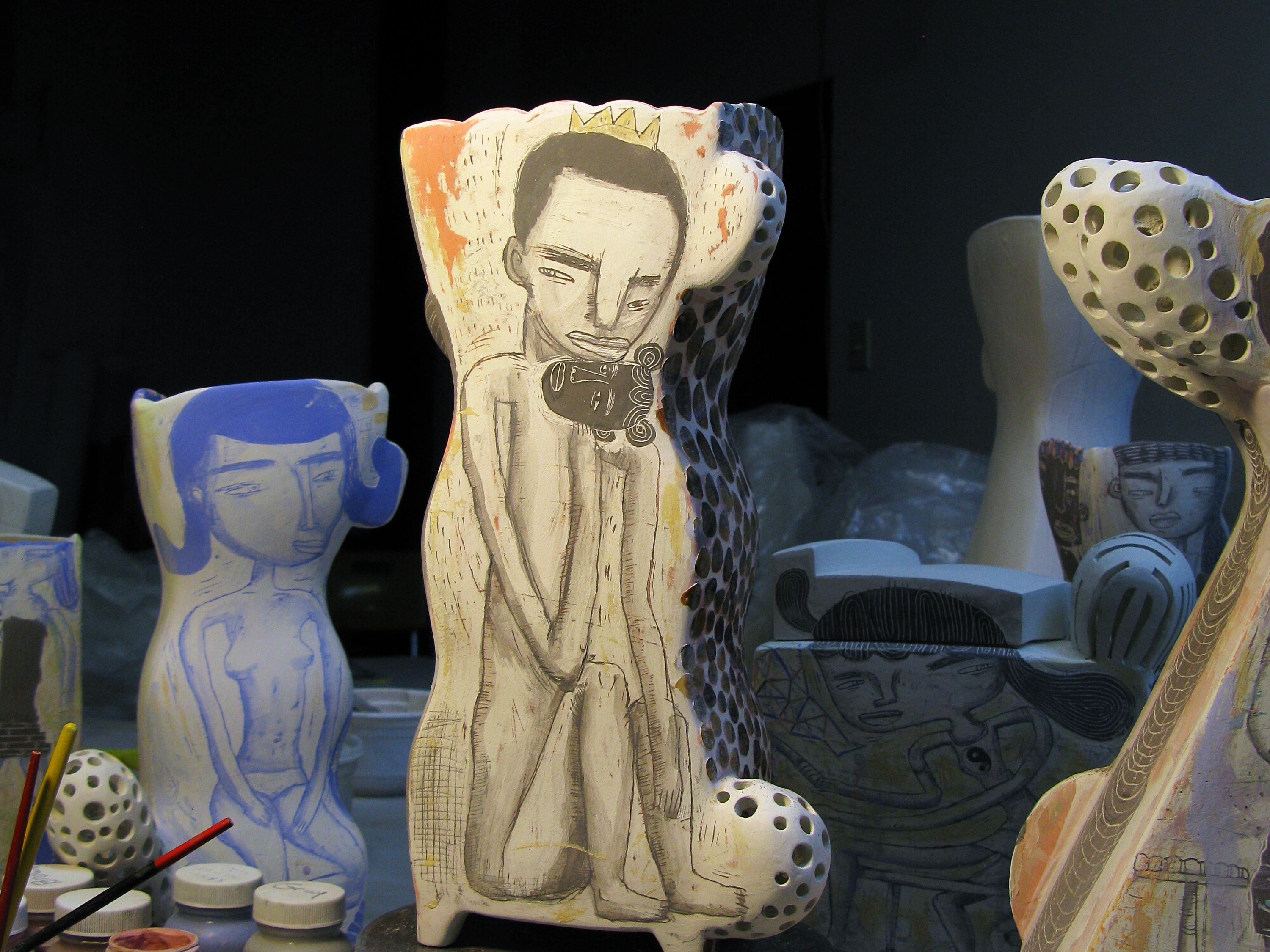 Studio shot of two ceramic vessels with hand drawn illustrations of a man and women