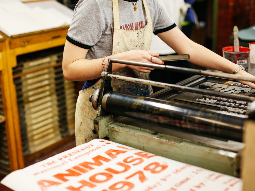 Student in apron working on the letterpress