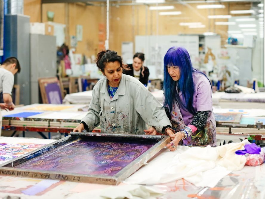 Technician and a student working on a fabric print in a fashion studio