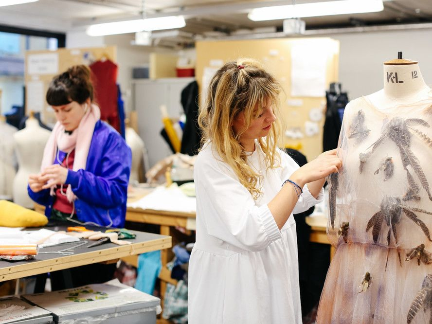 Girl working in studio, adjusting a garment on a mannequin