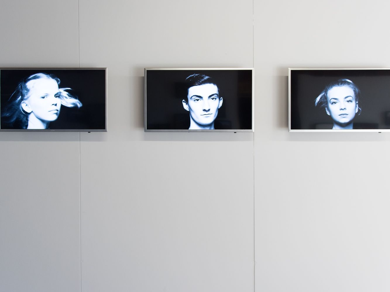 Three televisions mounted on a wall with videos of dancers spinning