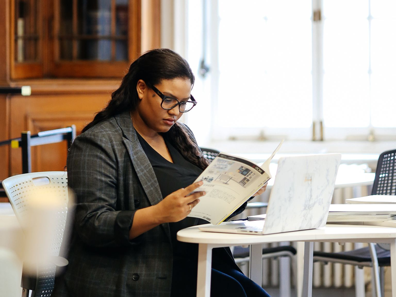 Student sitting at table in a bright library, looking through magazine and taking notes.