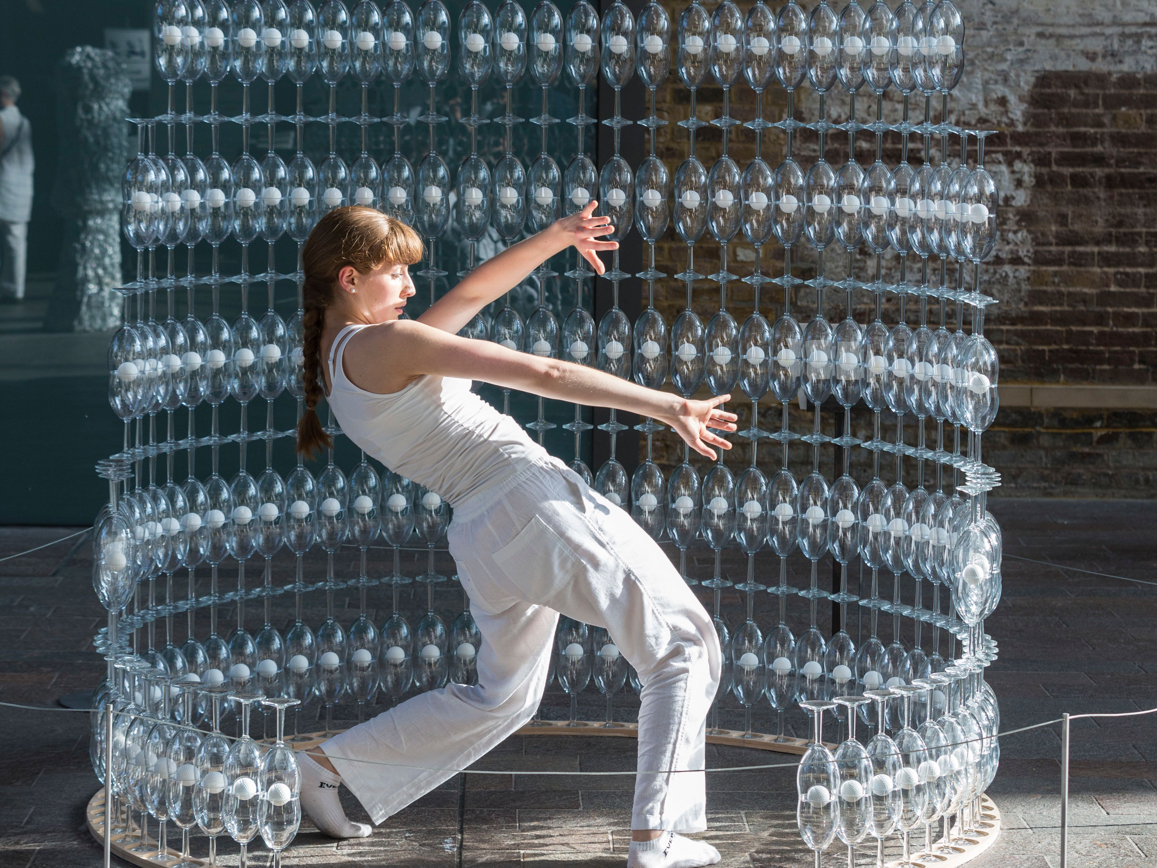 Image of a student doing a dance performance while surrounded by structure constructed from champagne glasses