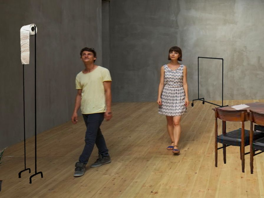 A room with a grey concrete wall and a light brown wooden planked floor. In the room there are two young people, one male with black short hair, wearing a yellow t-shirt, black jeans and black trainers, he is standing next to a woman who has the same colour hair that goes down to her chin and she has a fringe. She is wearing a white dress with a black pattern which goes horizontally across the dress. The length of the dress is above the knees with no sleeves, she also has on plain black sandals. The two people are looking around the room and are looking towards a large object which seems to be a large toilet roll holder taller than the two people with toilet roll at the top. In the room there is also a dark brown table with 4 matching chairs, each chair has four black cushions. There is a small open fridge on the floor plugged into a white wall socket ad there seems to be pieces of paper in the fridge. In the coroner of the room there is a tall plant sitting in a blue plant pot, there is a sculptured head in the pot, the sculptured head looks like the woman in the room and is connected to a large worm like tale, it sits in the plant pot. At the back of the room there is another mental frame similar to the toilet roll holder but is wider and looks more like a coat rack.