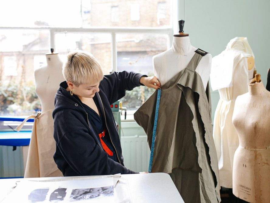Student testing garment on a mannequin in a fashion studio