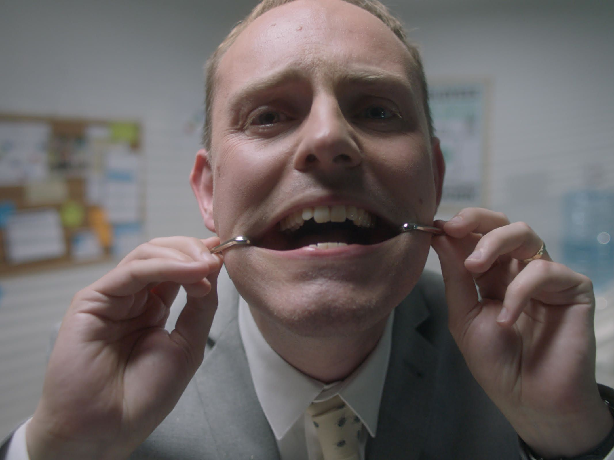 Close up of a man pressing a wire against his teeth