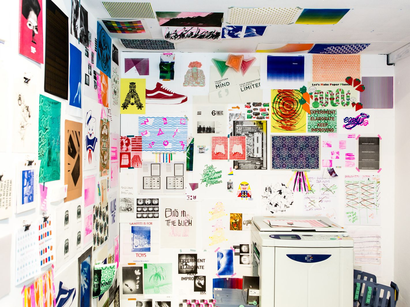 A shot of a corner of a white room full of colourful posters on the wall and ceiling, with a photocopier to the right