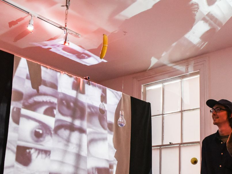 Photograph of a student interacting with a sound arts piece showing images multiple eyes projected onto a structure.