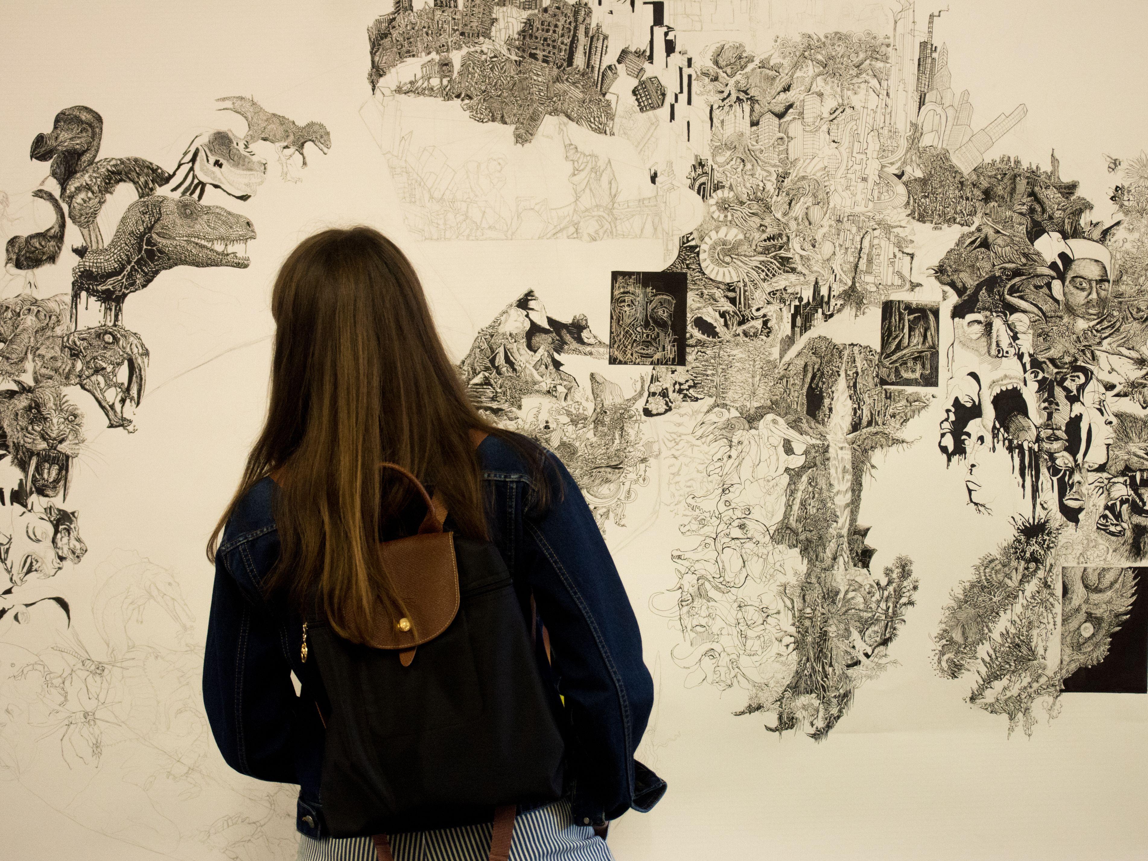 Person looking at artwork at Origins Creative Arts Festival