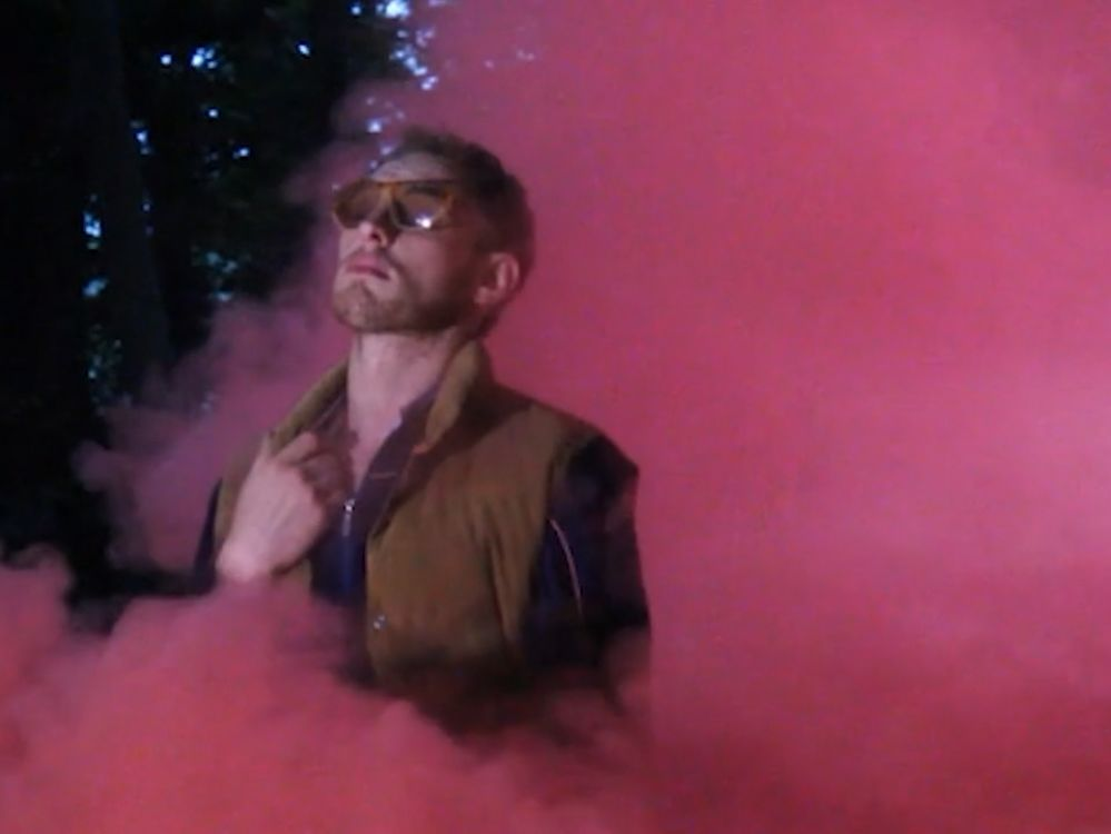 Luke Abbott stood among red smoke wearing sunglasses.