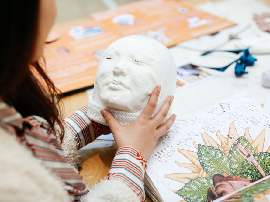 Student holding a cast of someone's face.