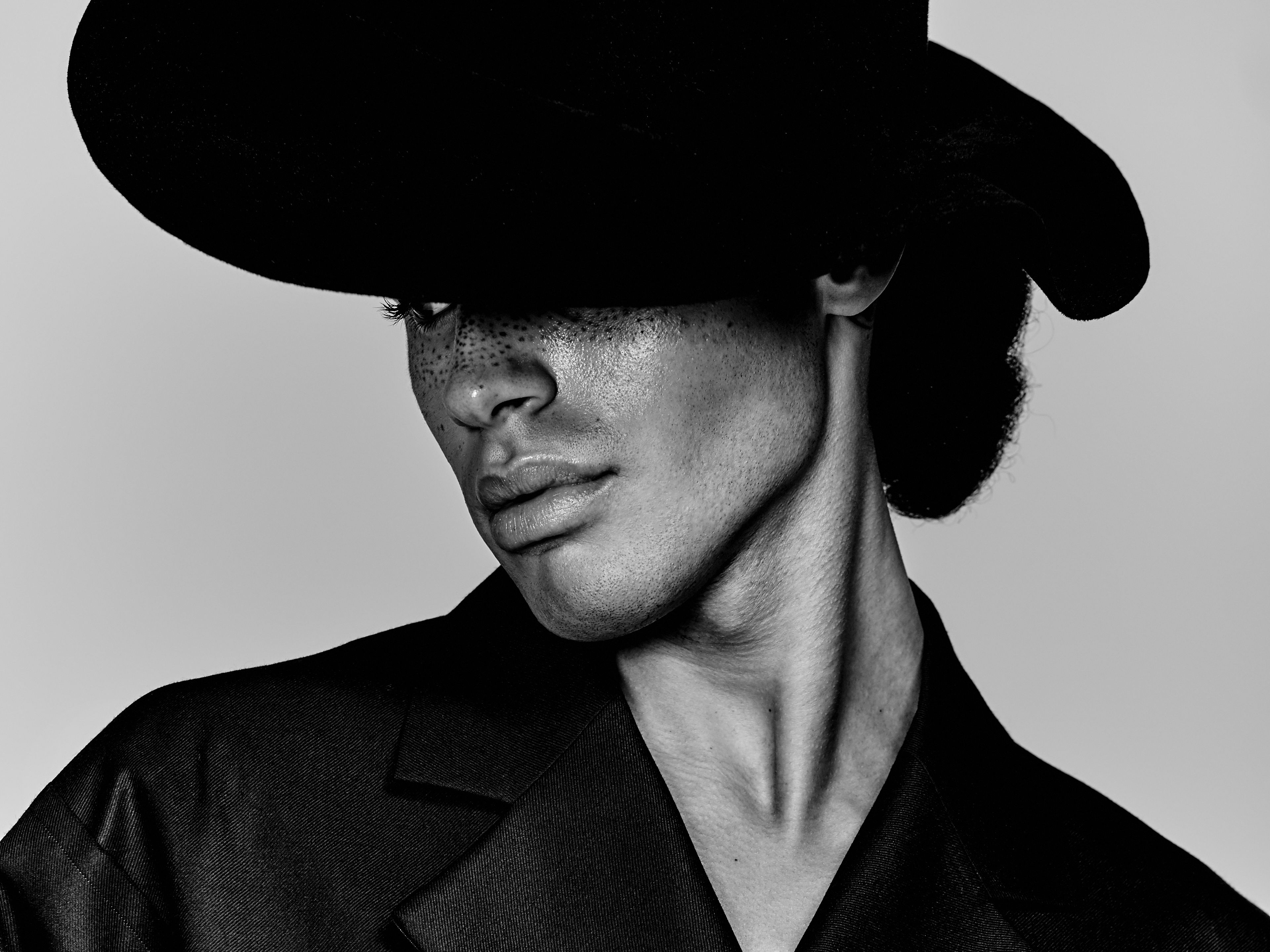 Black and white image of male model in wide brimmed hat