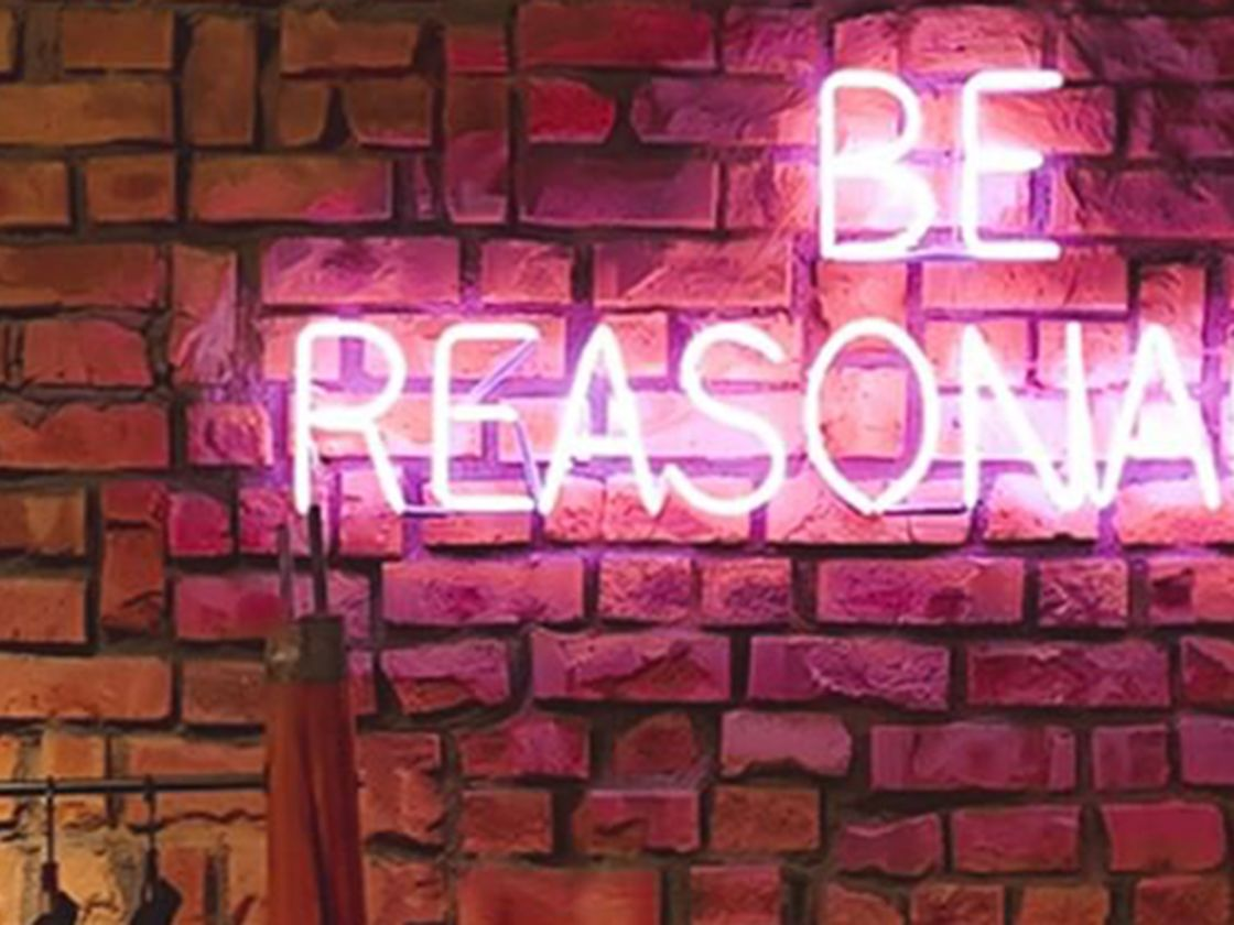 Be reasonable written in pink illuminous lights against a brick wall