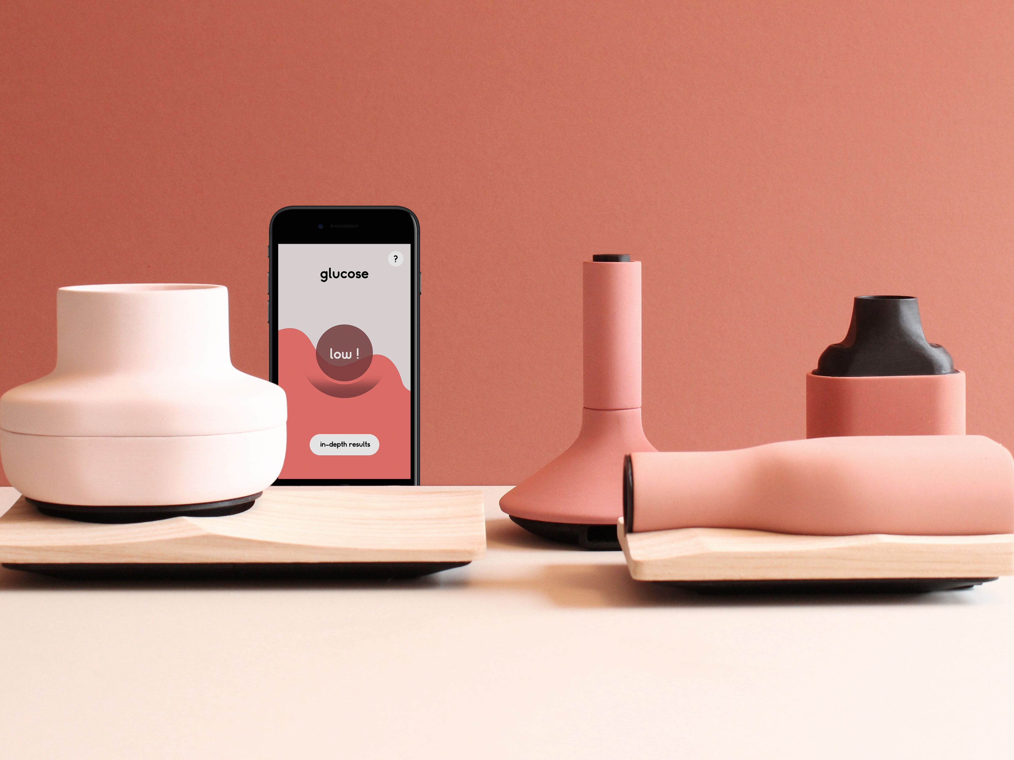 Pink and peach coloured ceramics arranged next to an iPhone