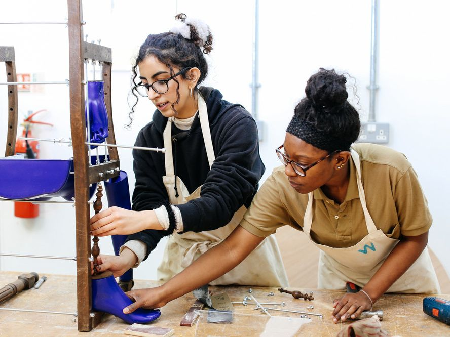 Two students creating a wooden structure