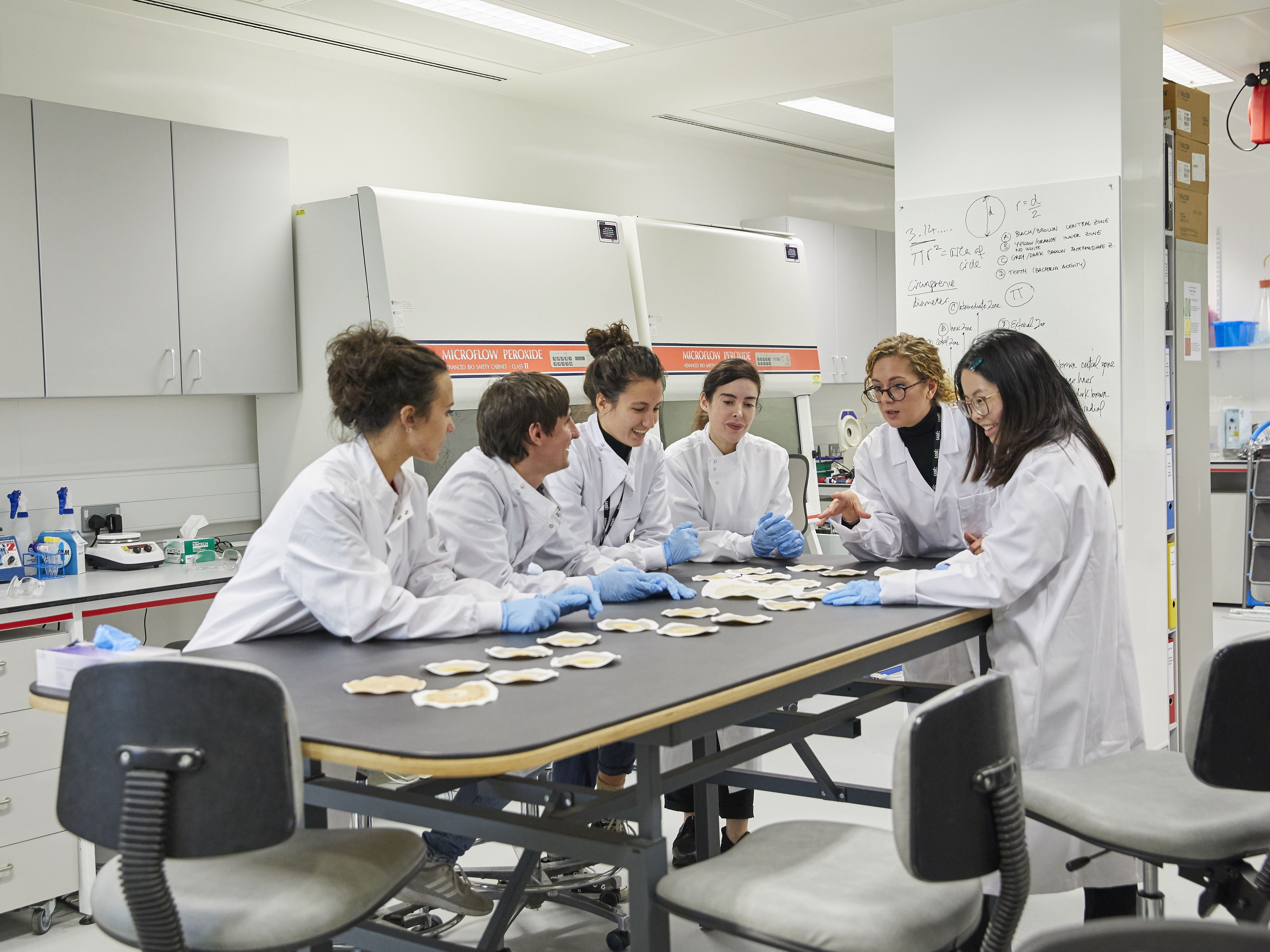 Students working in a lab wearing white coats