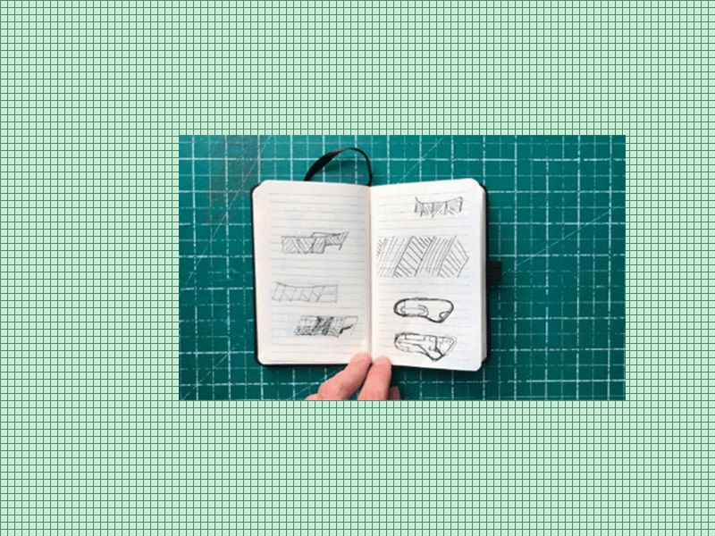 a small notebook with sketches, resting on top of a green cutting board