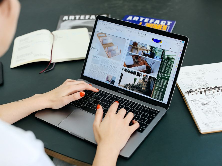 Student sitting at a desk using a computer to design creative media artwork