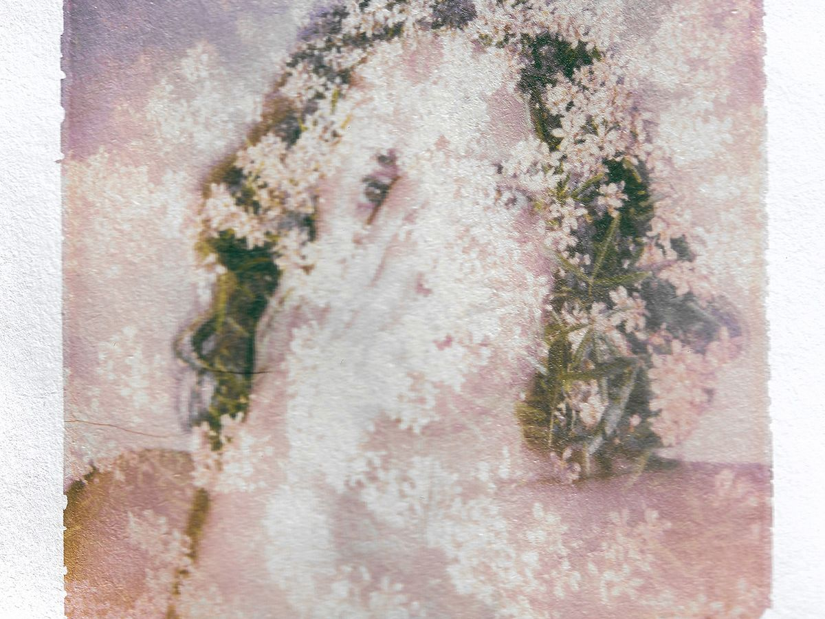 A blurred photograph of a woman.