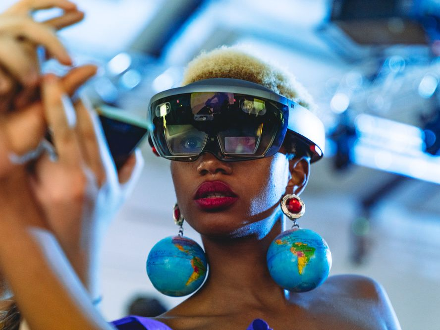 Woman wearing VR glasses and large, dangling globe earrings. We are looking upwards at her head and shoulders