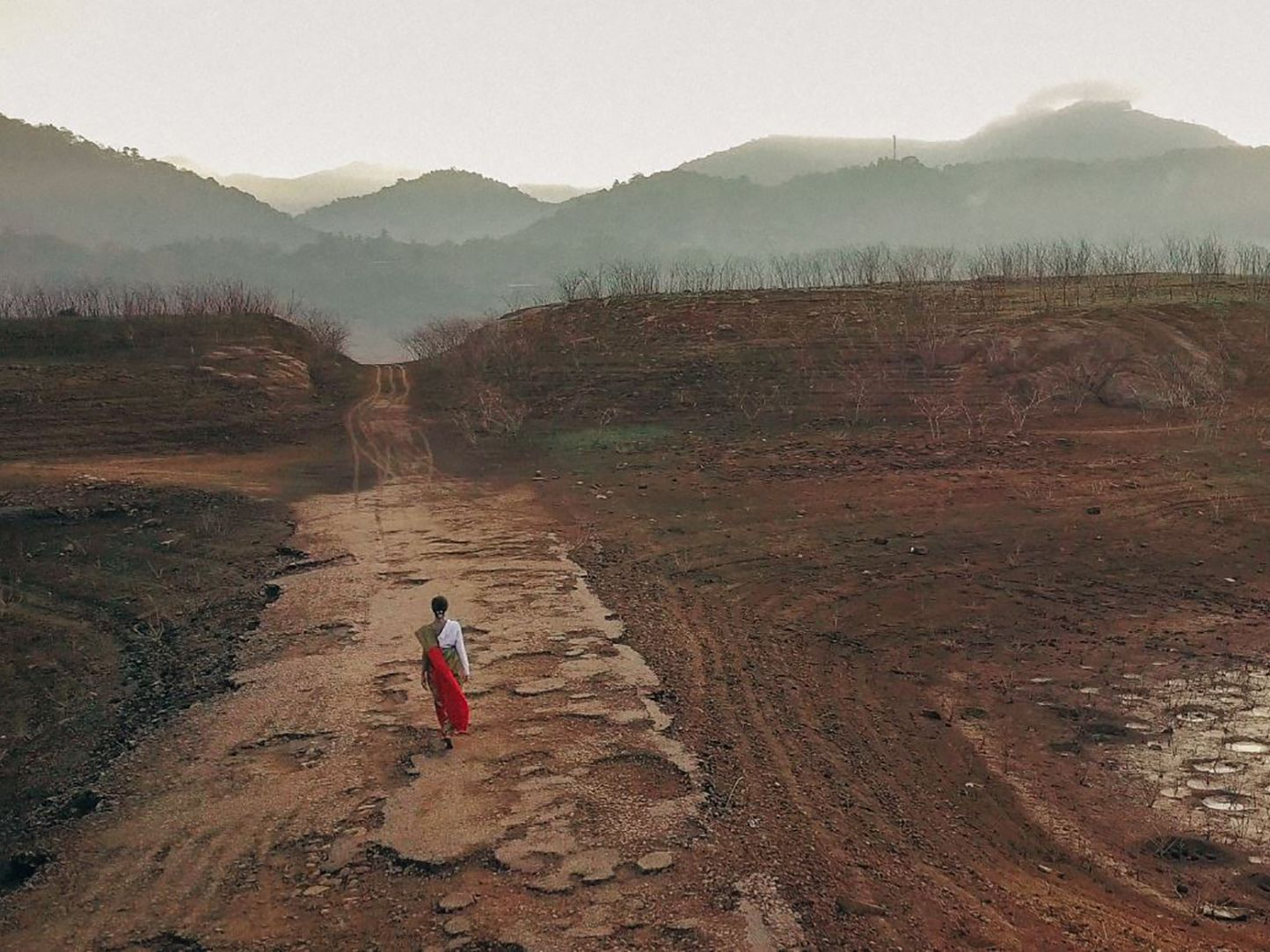 Indian woman wearing colourful clothes walking through derelict land