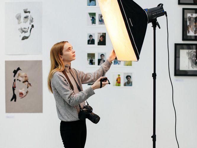 Female student adjusting a large softbox light.