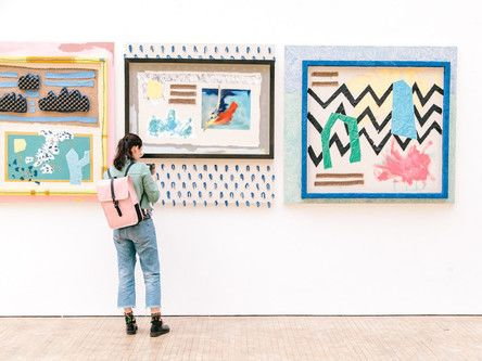A student looking at some art on a wall