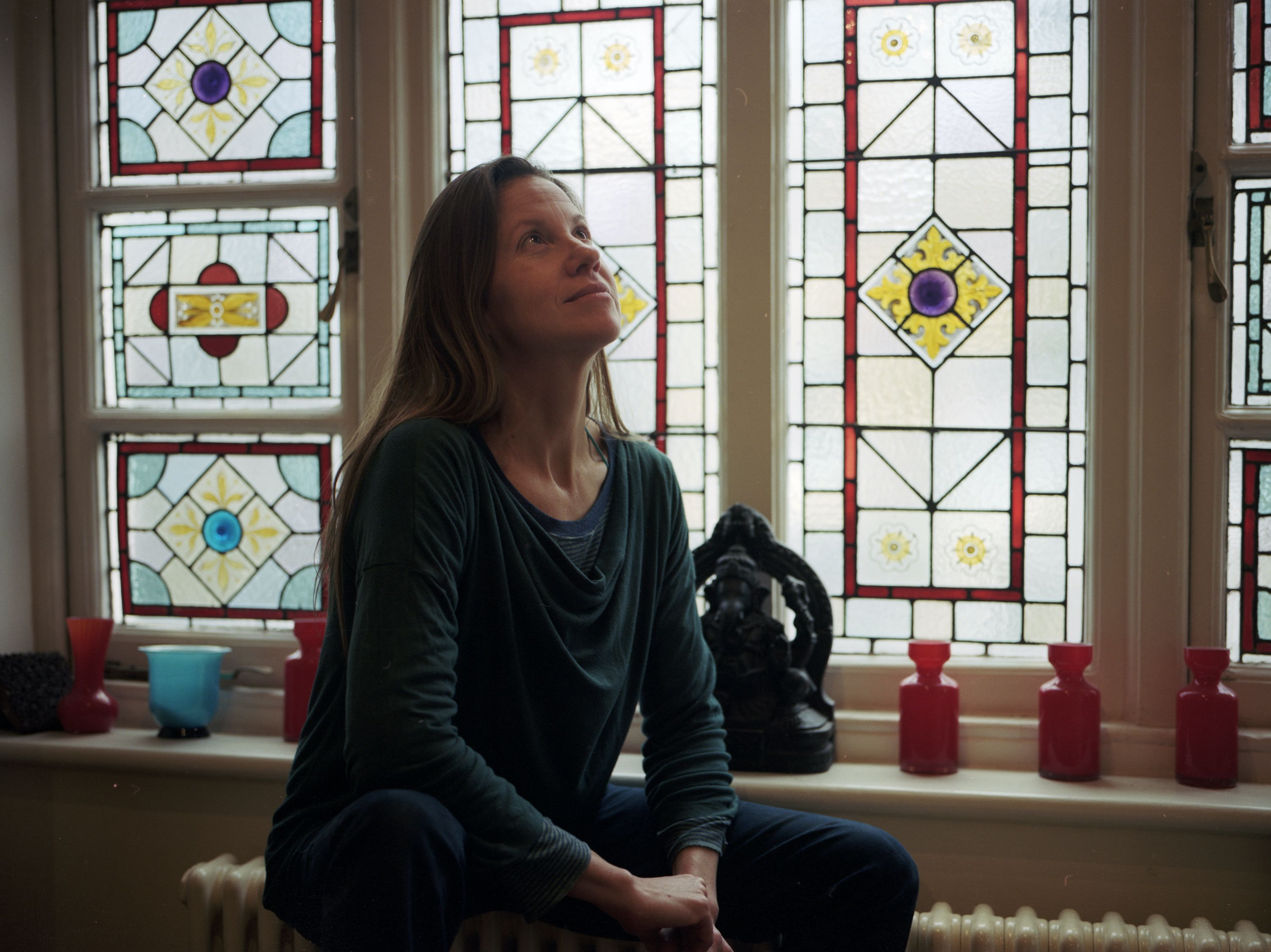 A woman sitting near a stain glass window
