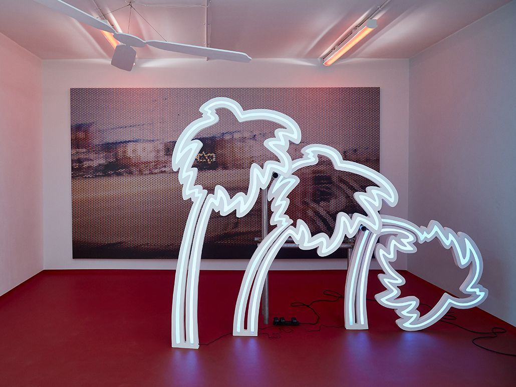 Installation with large scale photographic print and neon lit palm trees with red floor. By Sarah Entwhistle - Chelsea BA Fine Art.