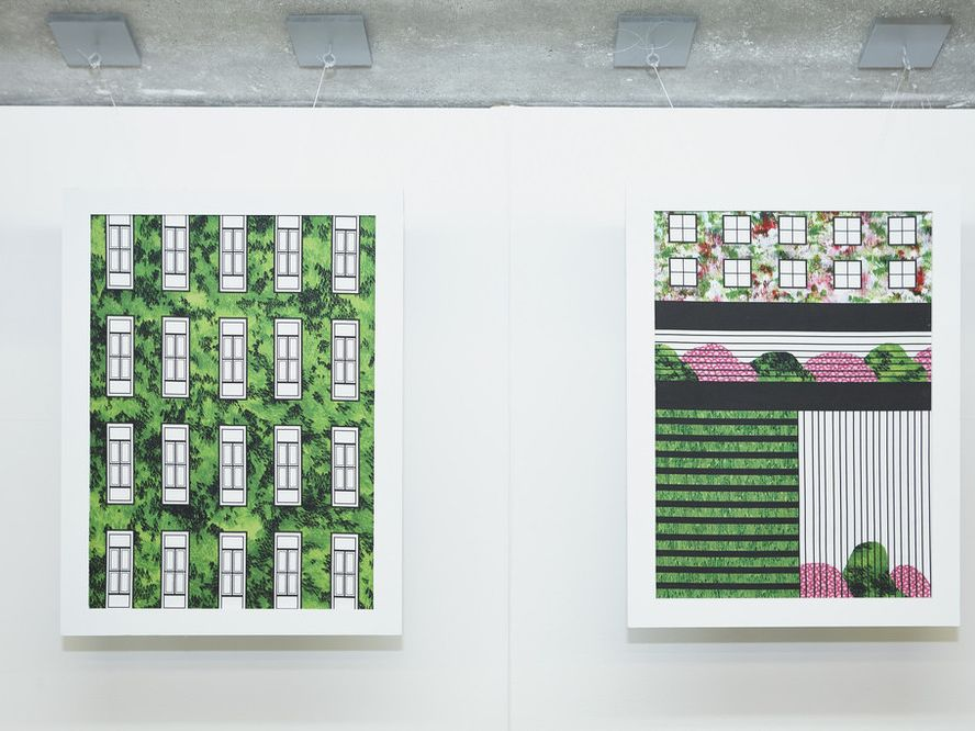 2 paintings in white frames on a white wall showing buildings and symmetrical designs integrated with the green of nature