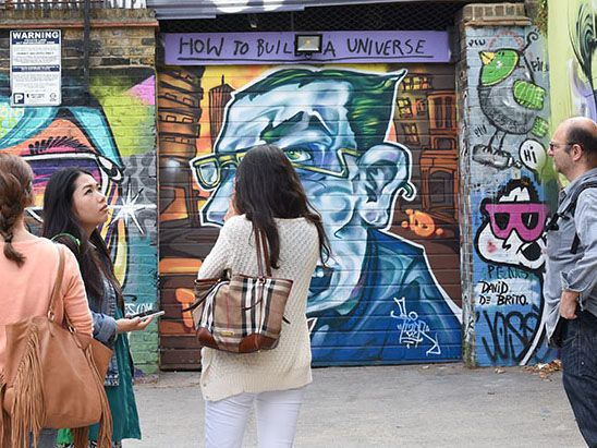 Group of people looking at a wall with graffiti on