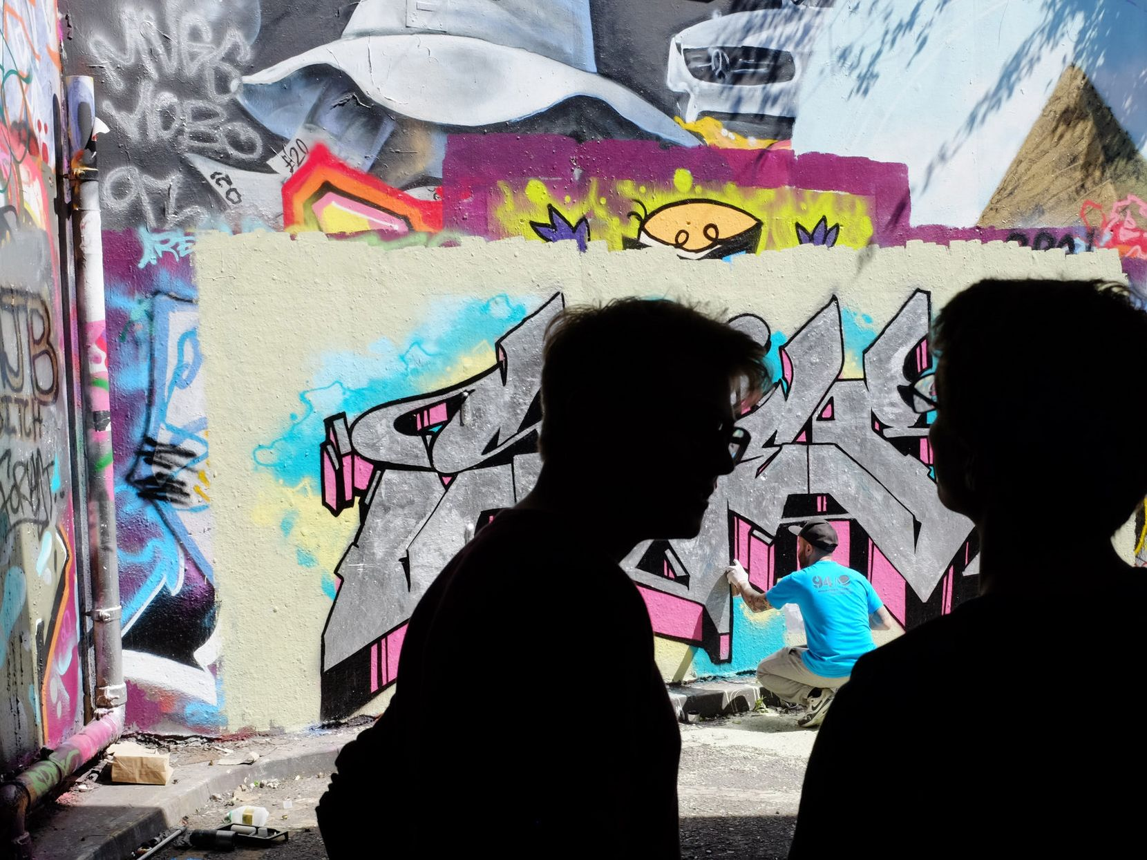 Two people watch a graffiti artist create work on an inner-city wall.