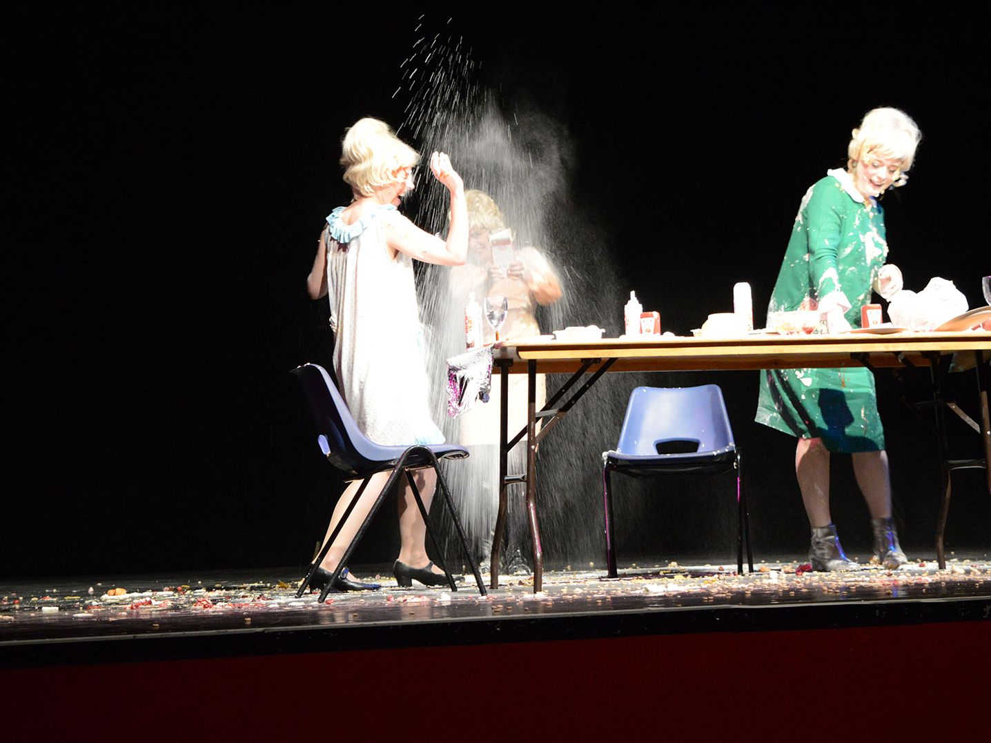 3 women dressed as Dusty Springfield having a food fight performance.