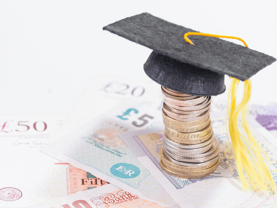Photograph of a stack of coins with a miniature graduation cap on top