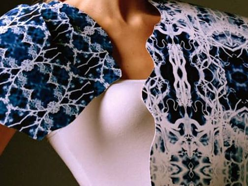 Female model wearing white top and white and blue printed cape