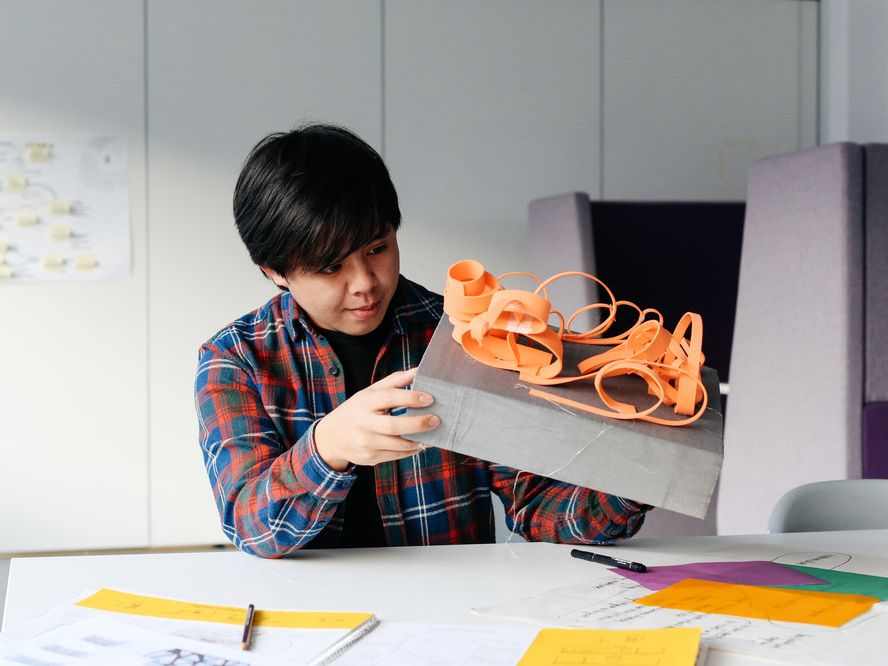 Student at a desk holding an orange sculpture