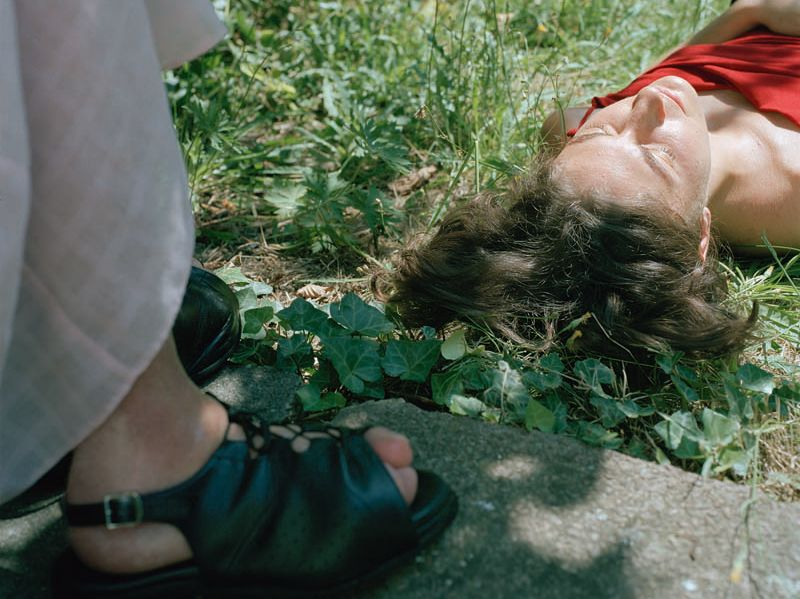Photograph of a woman lying on the grass next to a pair of feet