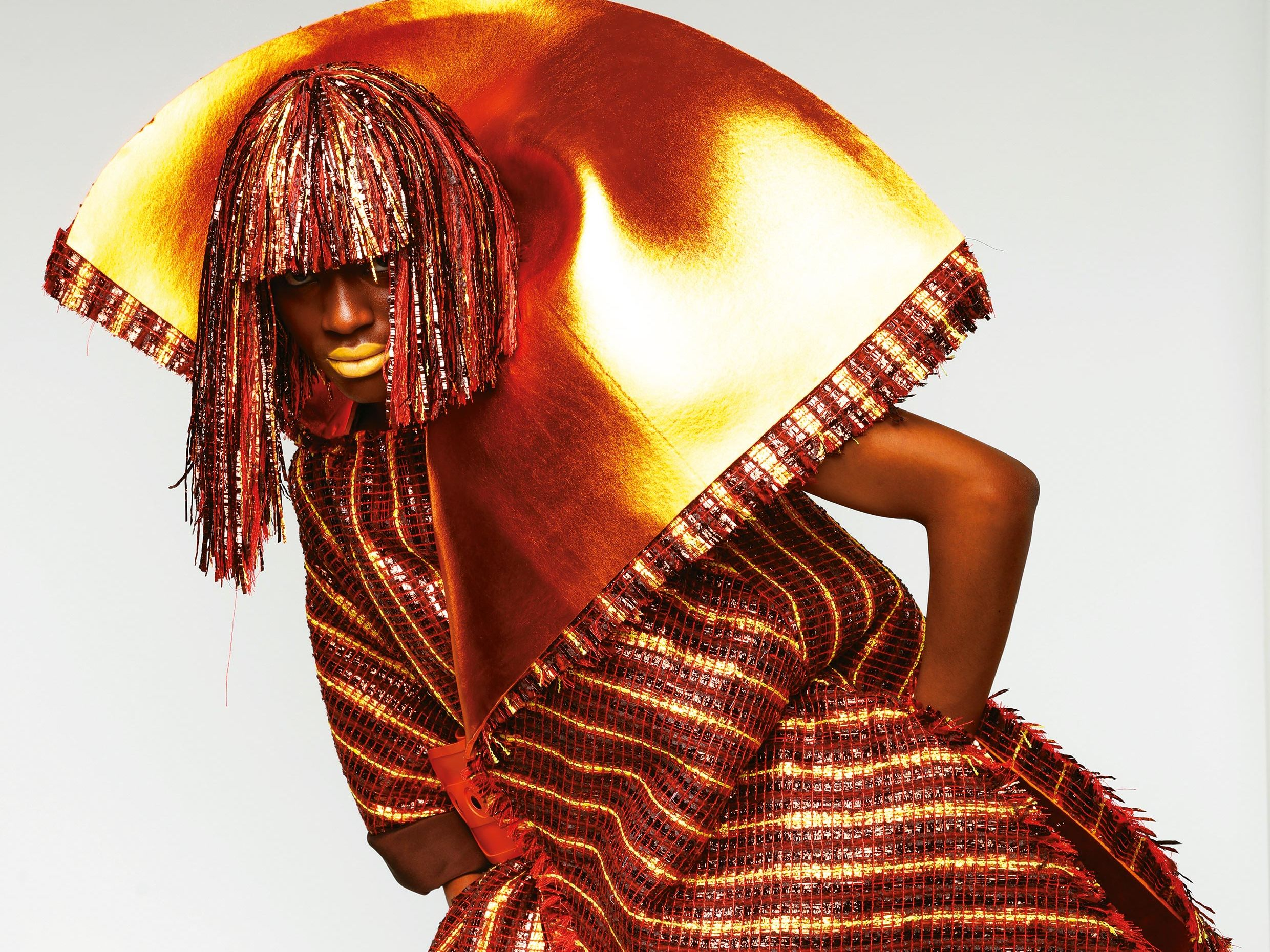 Woman wearing outfit woven in oranges and bronzes