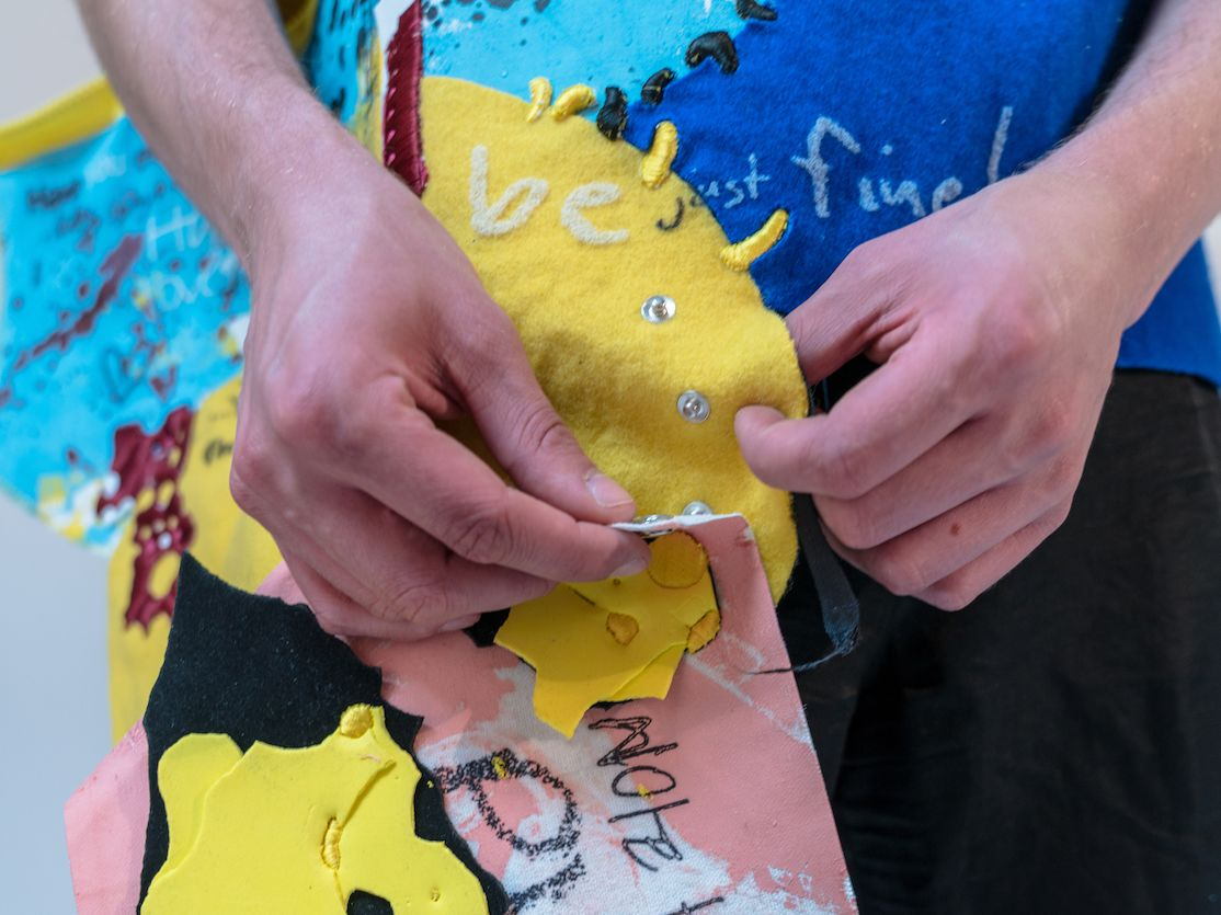 Two hands fixing a blue and yellow coloured garment