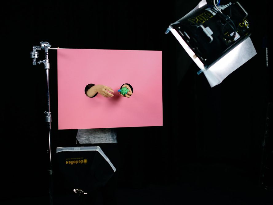 Student photography shoot of a pink screen with two arms sticking through two holes. The hands are playing with a green spiked ball.