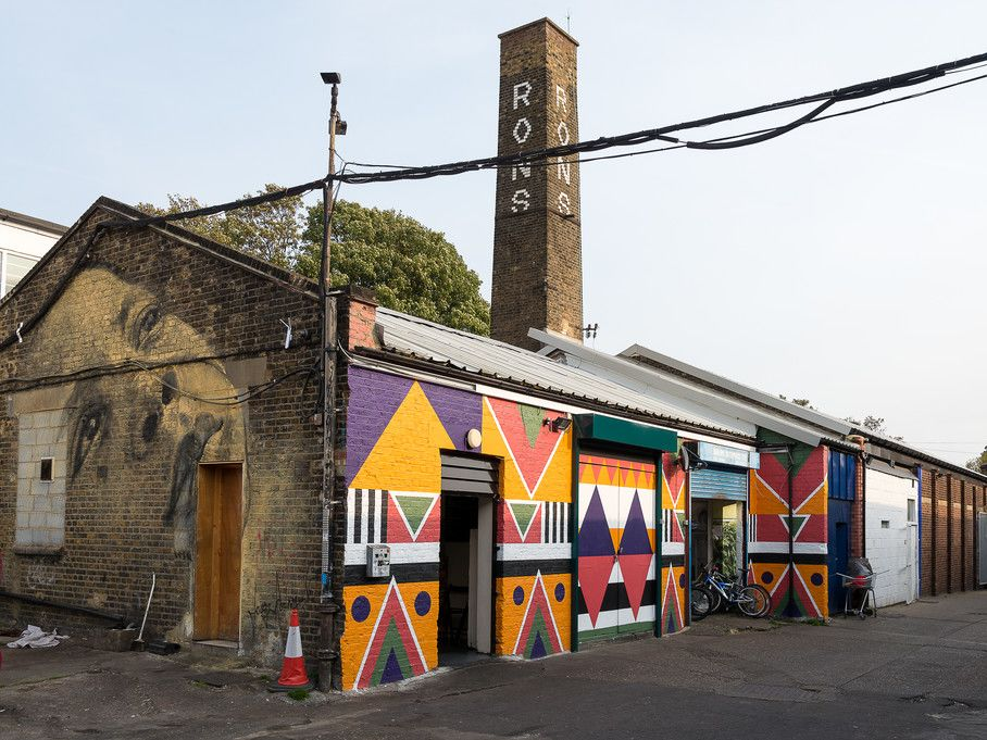 A row of low London premises covered in art on the front and side, shot from outside, with a bicycle in the doorway and a yard with a red bus just visible at the side
