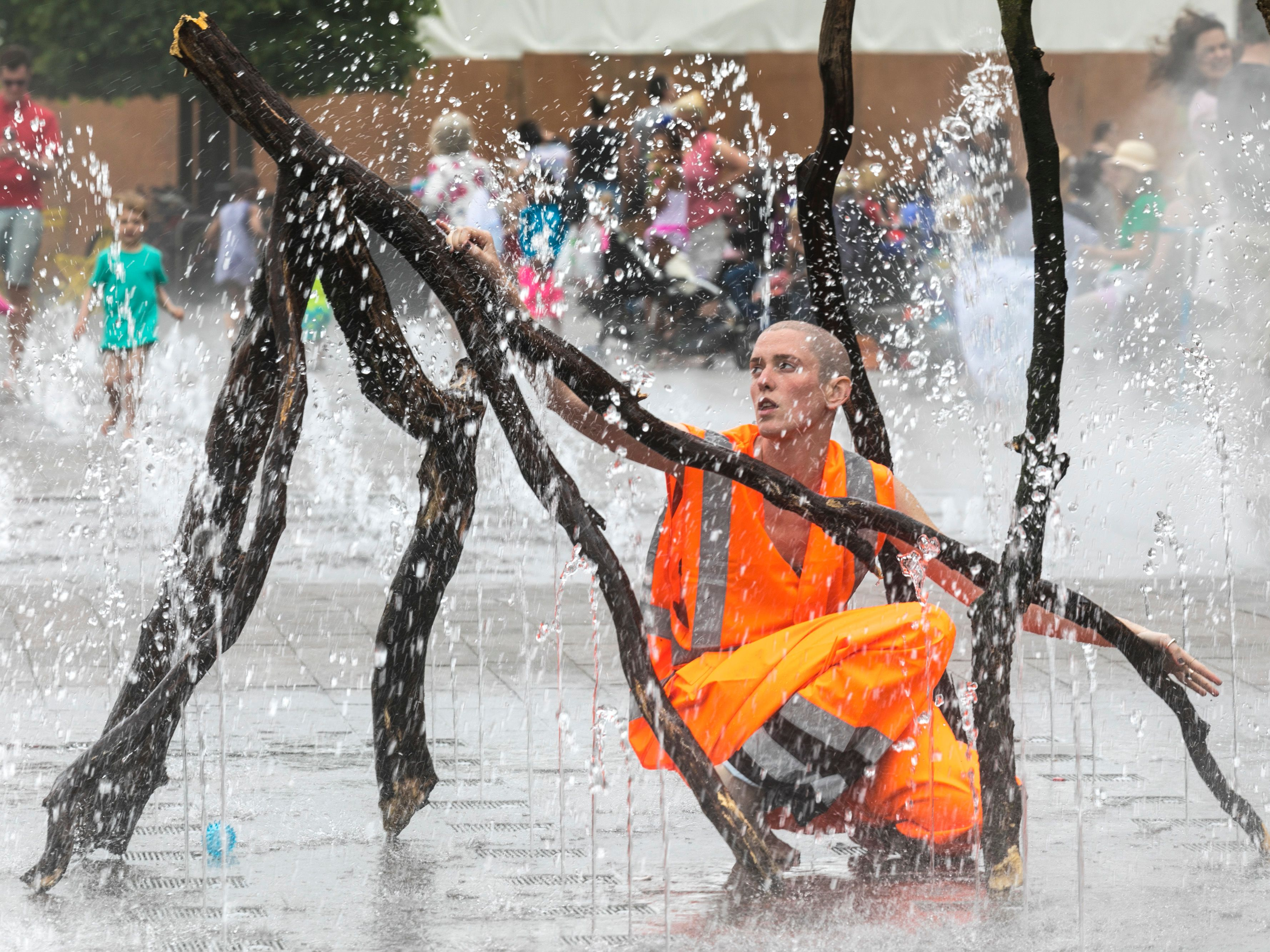 A person wearing an orange hi-vis jacket holding a branch in the Granary Square fountains