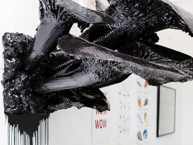 Large black sculpture mounted on a wall
