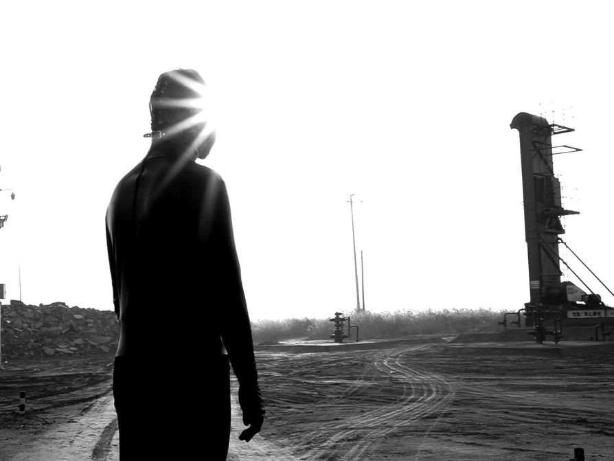 Person in a leather mask stands in front a industrial site in this black and white photo