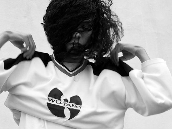A young man taking of a sweat shirt with a 'Wu-Tang' logo